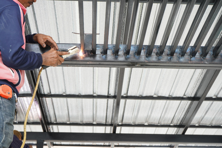 Welders are welding steel roof frame of home Standard-Bild - 107320974