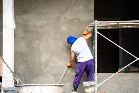 construction workers plastering building wall and beam using cement plaster mix of cement and sand at the construction site in thailand Standard-Bild - 107320996
