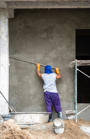 construction workers plastering building wall and beam using cement plaster mix of cement and sand at the construction site in thailand