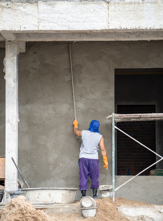 construction workers plastering building wall and beam using cement plaster mix of cement and sand at the construction site in thailand Standard-Bild - 107321001