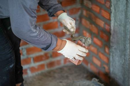 Close up of industrial bricklayer installing bricks on construction site in thailand Standard-Bild - 107320760
