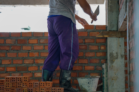 Close up of industrial bricklayer installing bricks on construction site in thailand