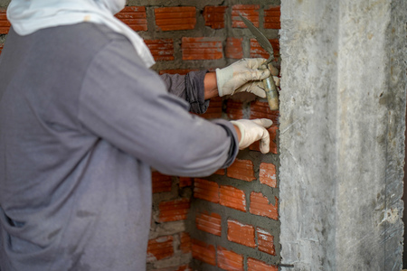 Close up of industrial bricklayer installing bricks on construction site in thailand Standard-Bild - 107320777
