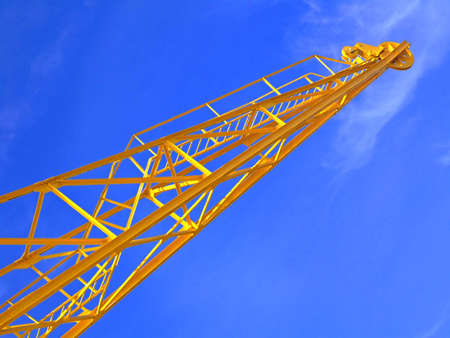 Bright yellow crane with blue sky in the background photo