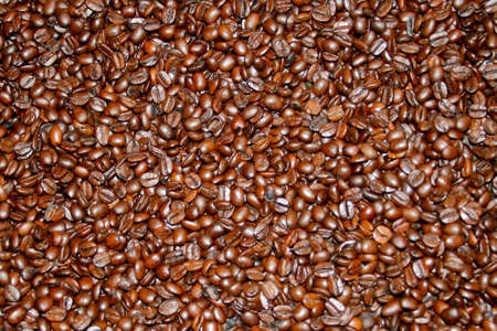 Dark brown fresh roasted coffee beans background