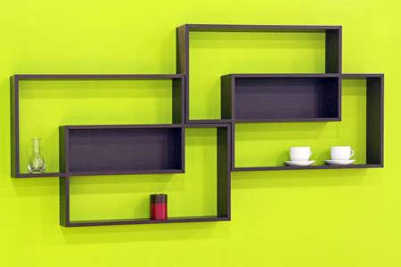 緑の壁の上の幾何学的なブラウン木製棚