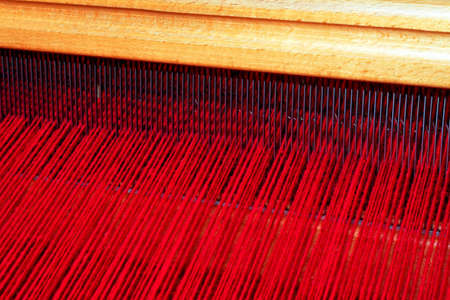 Close up shot of loom with red thread