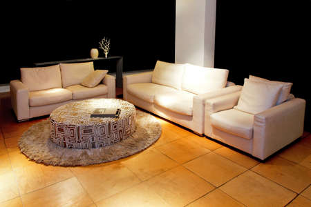 classic living room: Two classic sofas and armchair in living room at night