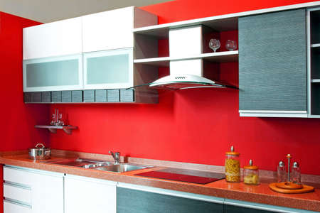 Contemporary red kitchen with big counter and ventilation
