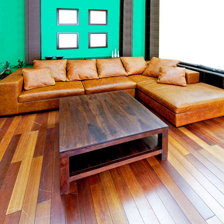 Green living room with brown leather sofa