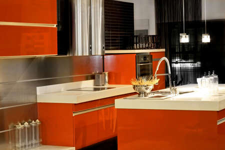 Red kitchen with big counter and metallic appliances Stock Photo - 3172174