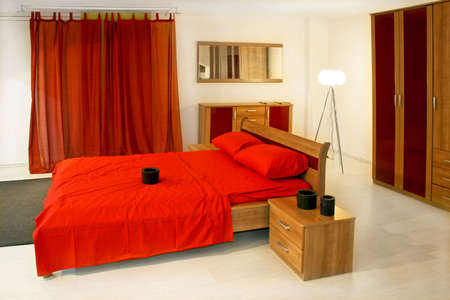 Bedroom with wooden furniture and red bedding photo