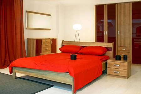 Bedroom with wooden furniture and red bedding Stock Photo - 3180576