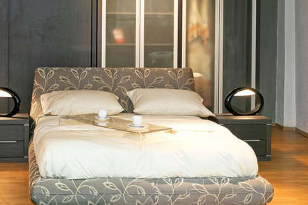 Modern double bed with served coffee cups photo