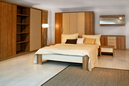 hotel bedroom: Standard bedroom in apartment with wooden furniture Stock Photo