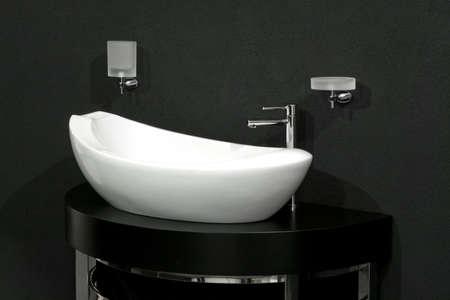 Oval shape white basin over black wall