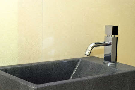 lavabo: Small grey granite basin and silver faucet