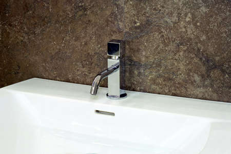 Water faucet in silver and white basin