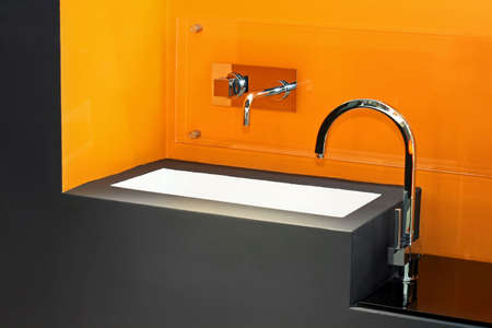 lavabo: Contemporary bathroom basin with vivid orange wall Stock Photo