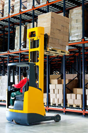 Yellow fork lifter with pallet in warehouse