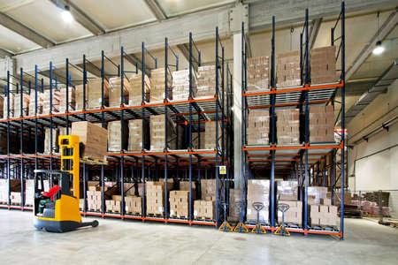 Yellow fork lifter work in big warehouse Stock Photo