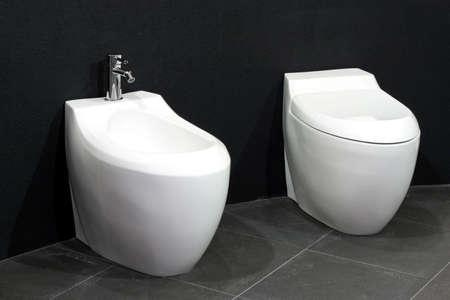bidet: White bidet and toilet over black wall Stock Photo