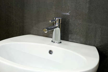 wash basin: Water pipe silver faucet and white basin Stock Photo