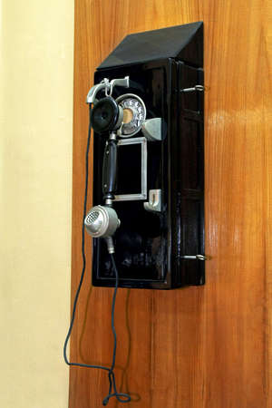 pay wall: Old black pay phone mounted on wall