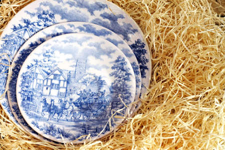 old english: Old English blue plates in hay reed
