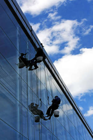 risky: Two windows cleaners hanging at risky work Stock Photo