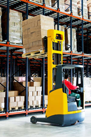 carretillas almacen: Elevador de horquilla amarilla con paleta en almac�n