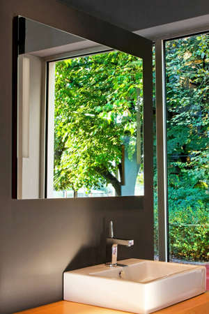 big window: Badkamer met groot raam en een groene tuin Stockfoto