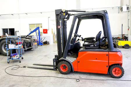 Red forklift vehicle in truck service garage photo