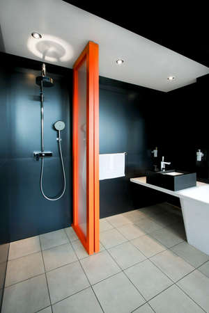 lavabo: Shower all in black with orange divider Stock Photo