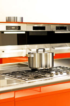 Stainless steel pot at stove in red kitchen photo