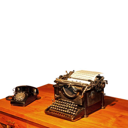Wooden desk with typewriter and old phone photo