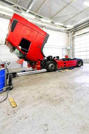 Open red truck in big service garage photo