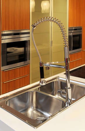 double oven: Modern kitchen faucet with oven in background