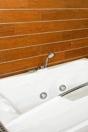 Big modern bathtub with wooden background wall photo