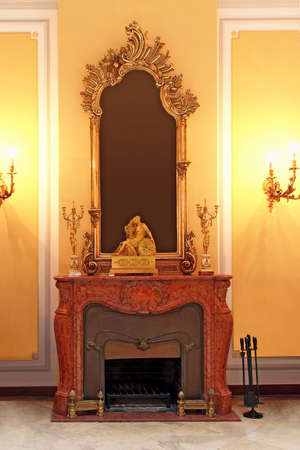 Medieval style marble fireplace and golden mirror photo