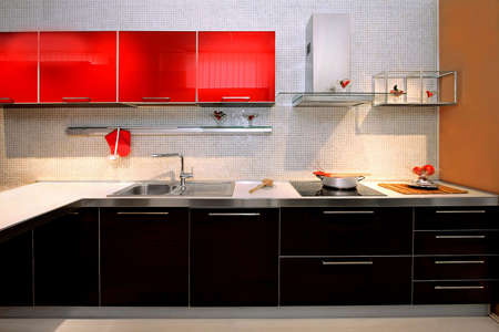 kitchen cupboard: Interior of red kitchen with contemporary counter Stock Photo