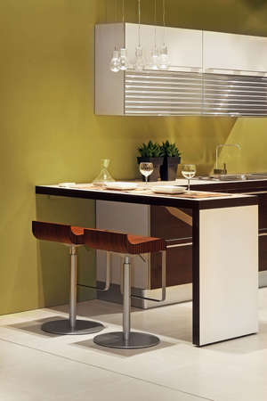 Modern kitchen with counter bar and two chairs photo