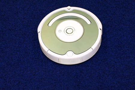 Modern robot vacuum cleaner at blue carpet Stock Photo - 4820692