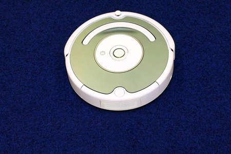 Modern robot vacuum cleaner at blue carpet Stock Photo - 4820692