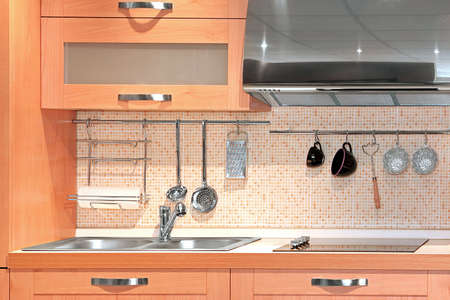 Detail of compact kitchen in light wood photo