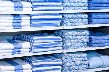 linen fabric: Big pile of blue towels at shelf