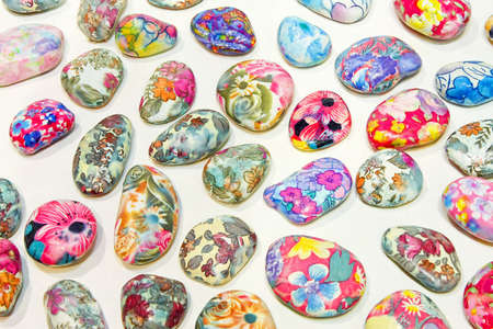 Bunch of colorful hand painted decorative pebbles photo