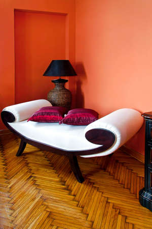 settee: White settee in orange living room interior