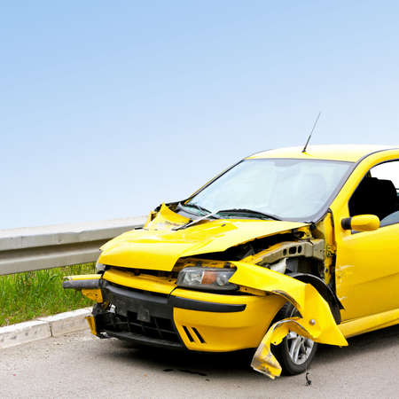 road to recovery: Front view of crashed yellow car at highway Stock Photo