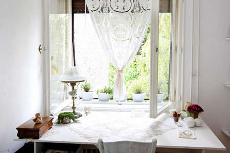 window curtains: Close up shot of white table under window